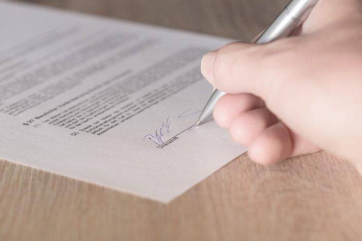 Mann unterschreibt Vertrag